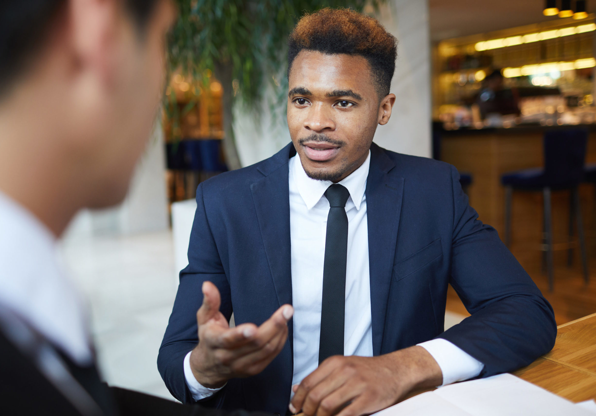 African young businessman has an interview with business partner in informal setting