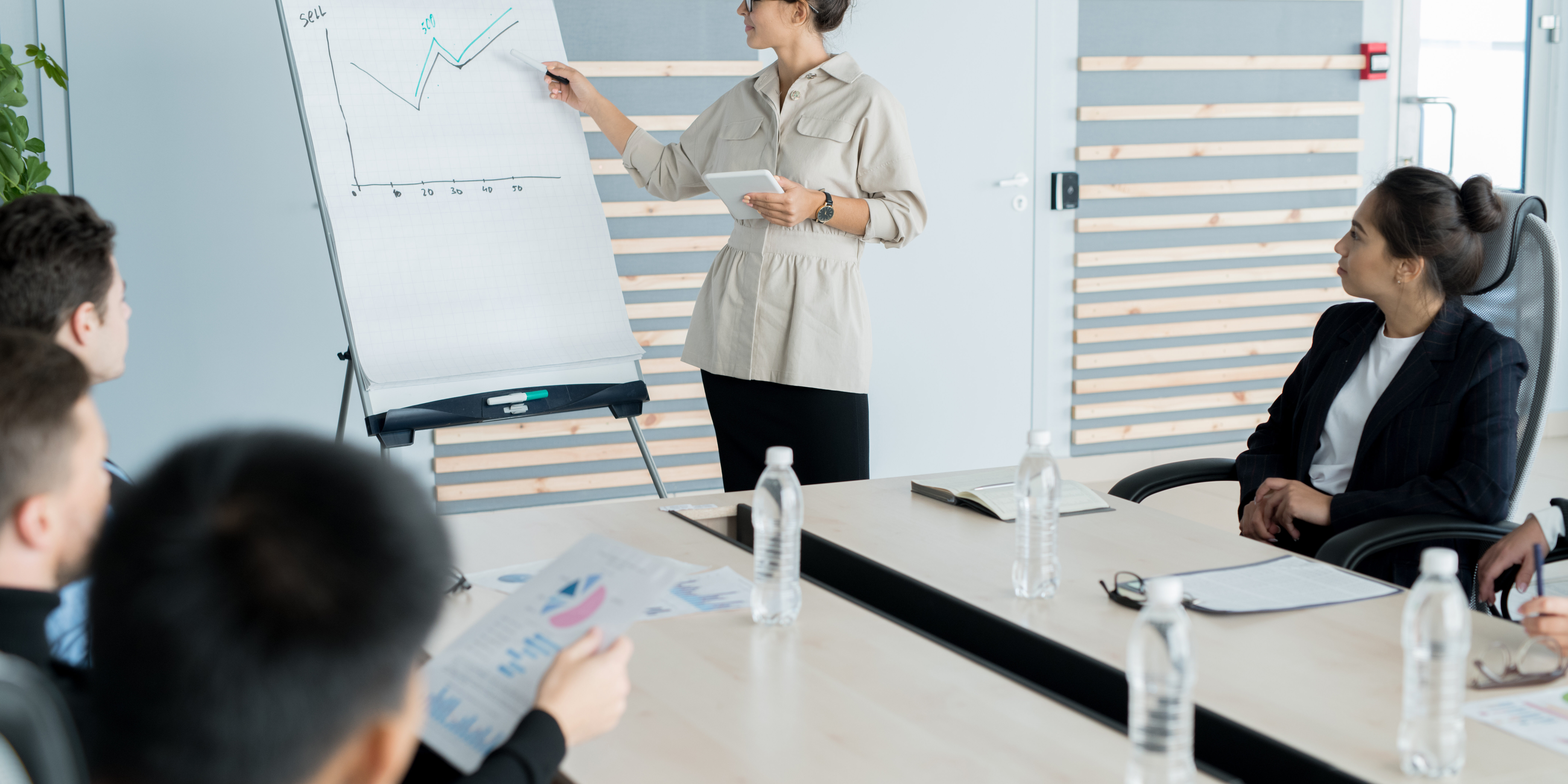 Young sales coach with hair bun wearing glasses holding presentation and explaining graph to business people at training class